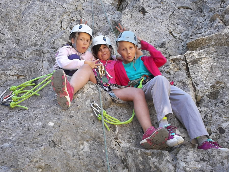 trois fillettes faisant de l'escalade en colonie de vacances à la campagne
