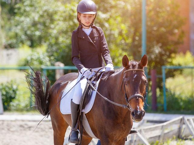 Jeune fille à cheval en stage sportif