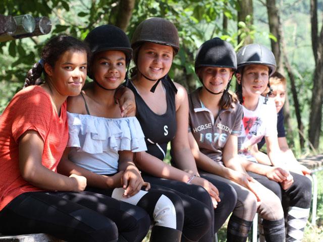 Groupe de jeunes filles pratiquant l'équitation en colo