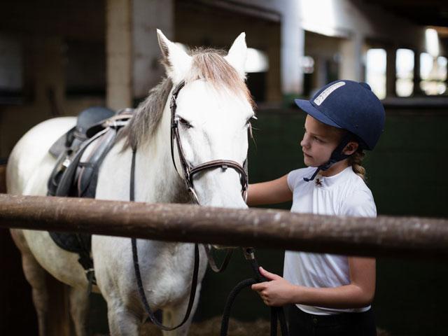 Portrait d'un enfant et son cheval au centre équestre