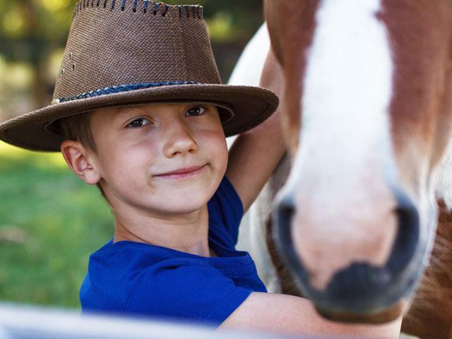 Enfant avec son cheval en stage sportif
