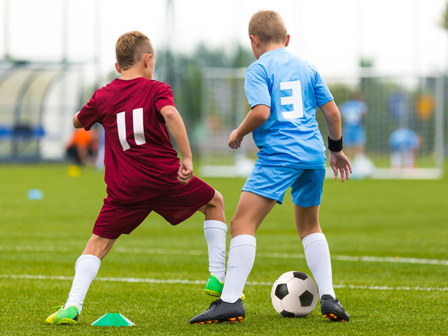 Enfant jouant au football en stage sportif