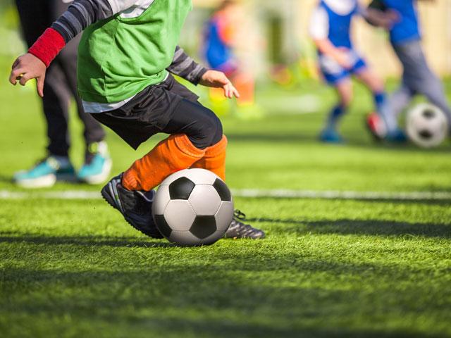 Enfants de 9 ans apprenant à jouer au football