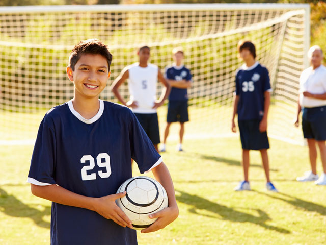 Adolescents jouant au football en stage sportif
