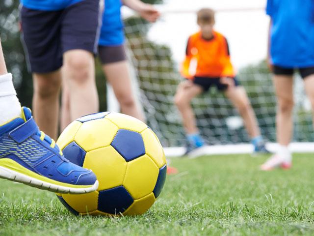 Ados jouant au football en stage sportif