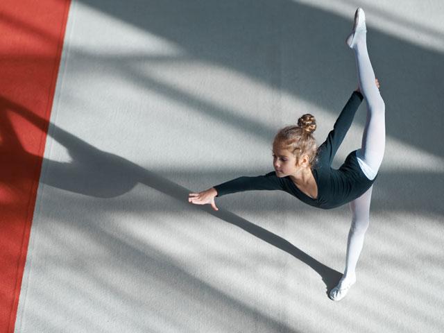 Enfant qui suit des cours de gymnastique en stage sportif