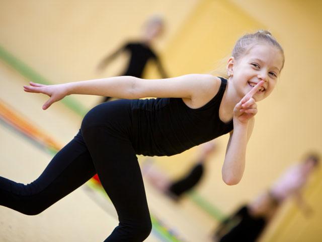 Jeune fille heureuse de faire de la gymnastique en colonie de vacances