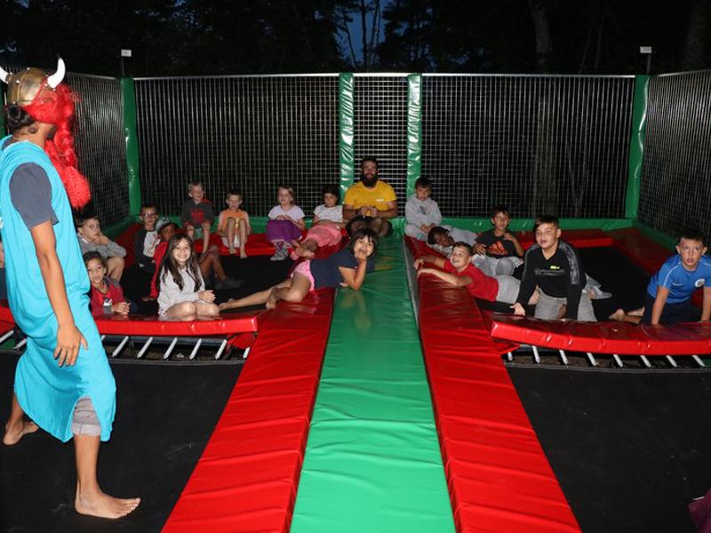 Enfants et leur animateur de colonie de vacances faisant du trampoline