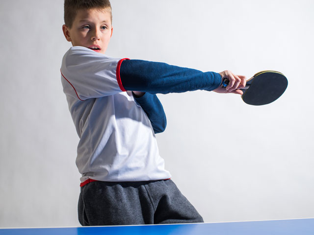 Enfant jouant au tennis de table en stage