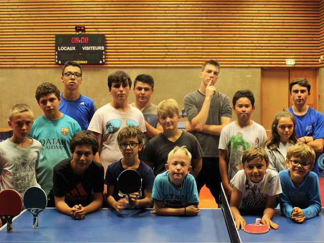 Groupe d'enfants pratiquant le tennis de table en colo
