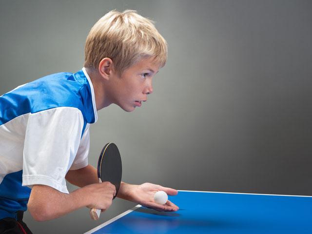 Enfant qui pratique le tennis de table à haut niveau en colo