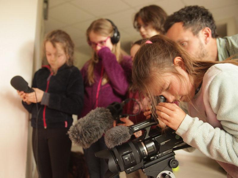 enfants apprenant à se servir d'une caméra professionnelle en colonie de vacances cinéma