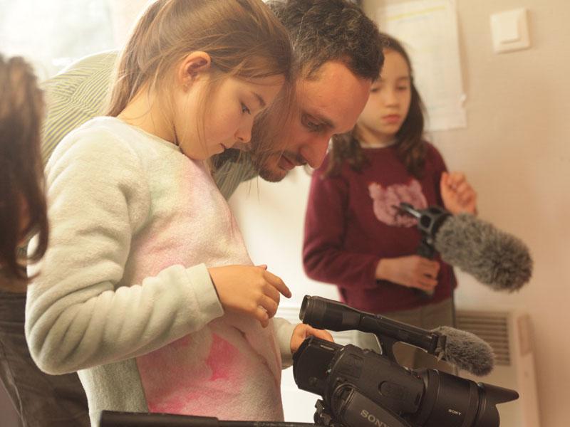 Animateur apprenant à une fillette de colo à se servir d'une caméra professionnelle