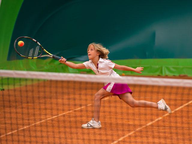 Jeune fille apprenant à jouer au tennis en stage sportif à yssingeaux
