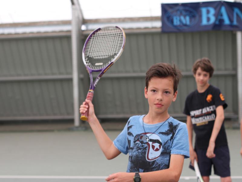 Enfant jouant au tennis en colo