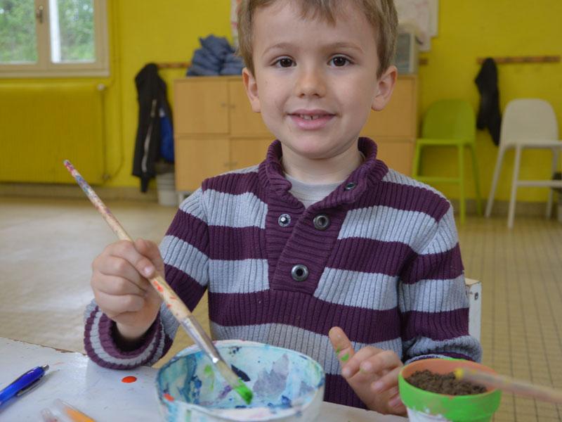 enfant faisant de la peinture en colonie de vacances à la ferme