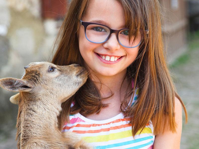 Portrait d'une fillette avec une chèvre en colonie de vacances