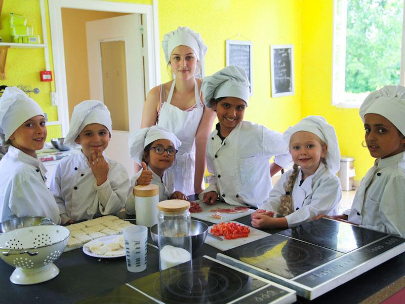 groupe d'enfants en train de cuisiner en colonie de vacance ce printemps