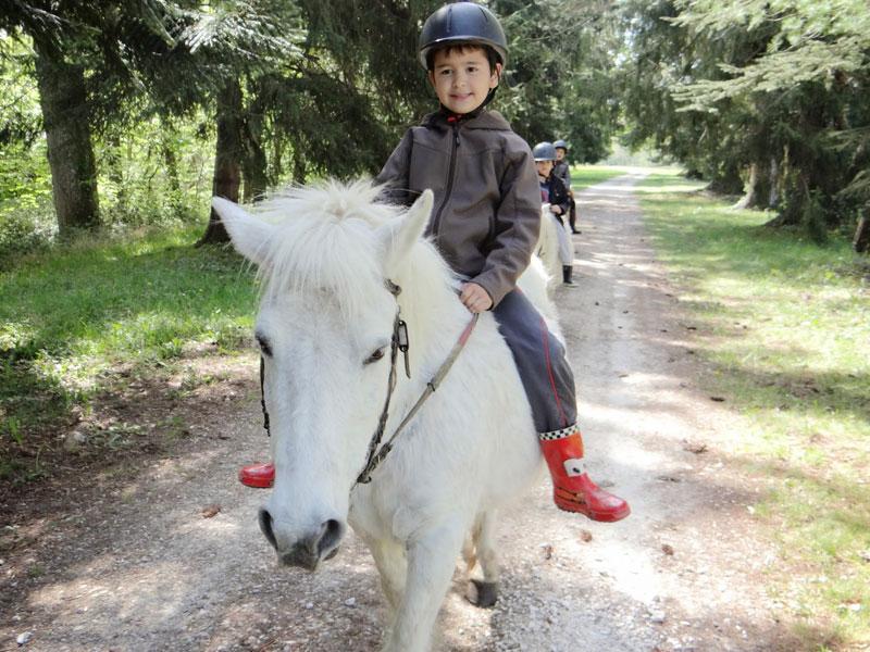 Jeune enfant à cheval à la campagne en colonie de vacances ce printemps