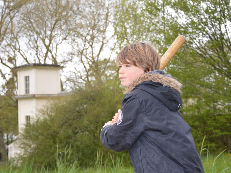 Portrait d'un jeune garçon jouant au baseball en colonie de vacances pour apprendre l'anglais en France