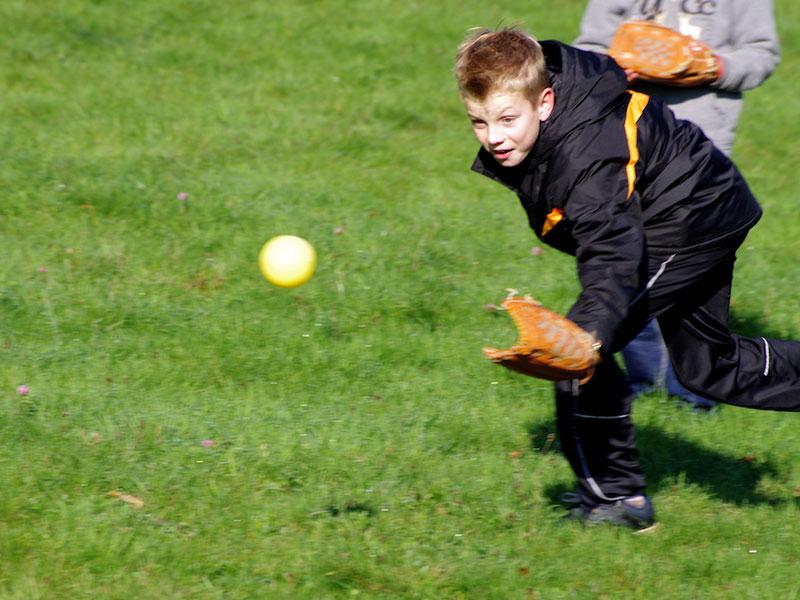Enfant en train d'attraper la balle au baseball en colonie de vacances pour apprendre l'anglais en France
