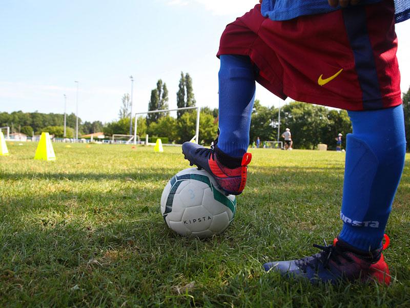 Vue sur les pieds d'un enfant portant une tenue de football en colonie de vacances multisports au printemps