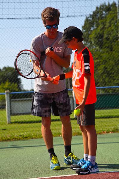 Entraineur de tennis apprenant au jeune à jouer  en colonie de vacances multisports au printemps
