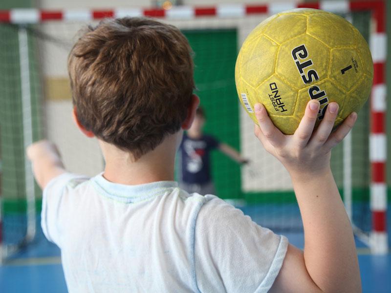 Enfant jouant au handball en colonie de vacances multisports au printemps
