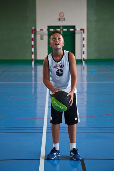 Jeune preado preparant son lancer durant une partie de basketball en colonie de vacances multisports au printemps
