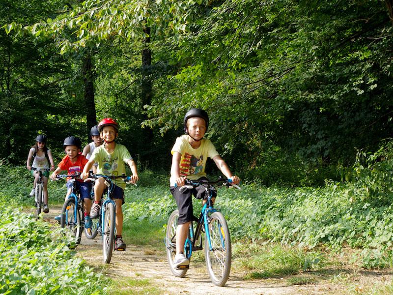 groupe d'enfants en randonnée à vélo en colonie de vacances multisports au printemps