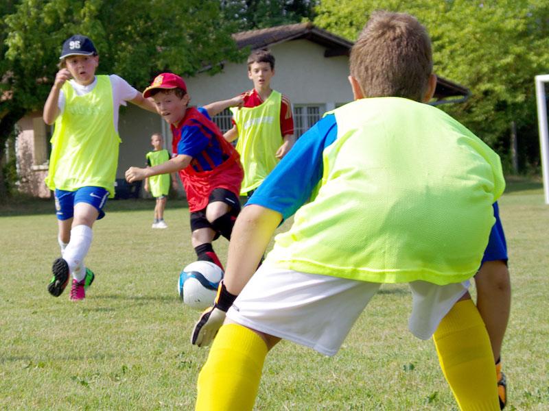 enfant occupant le role de gardien de but au football en colonie de vacances multisports au printemps