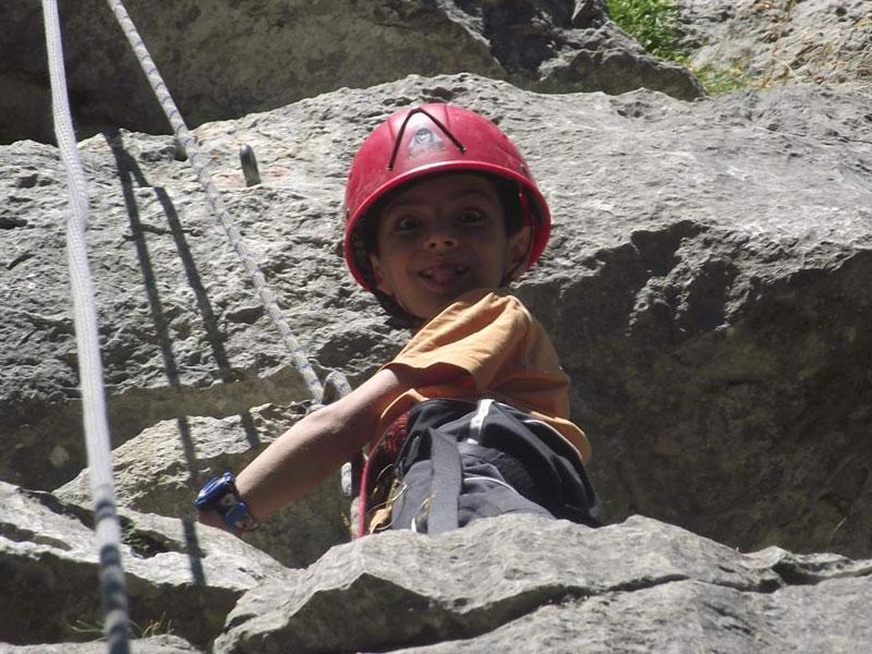 Portrait d'un enfant faisant de l'escalade en colo