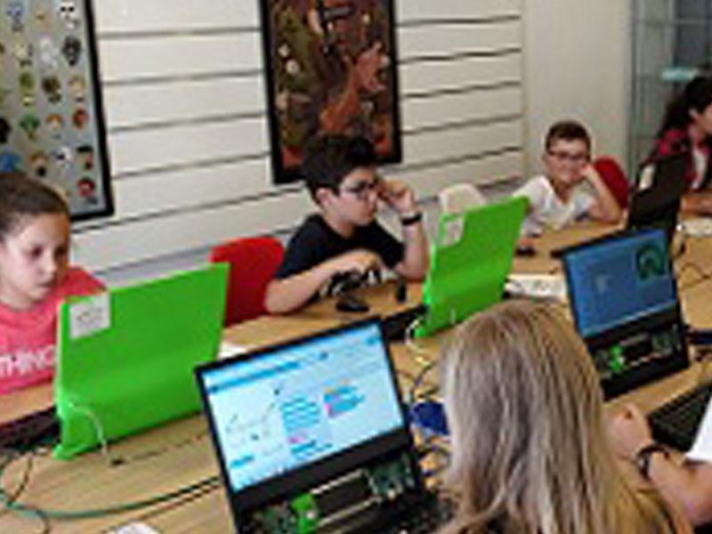 groupe d'enfants sur ordinateurs apprenant à créer un jeu vidéo