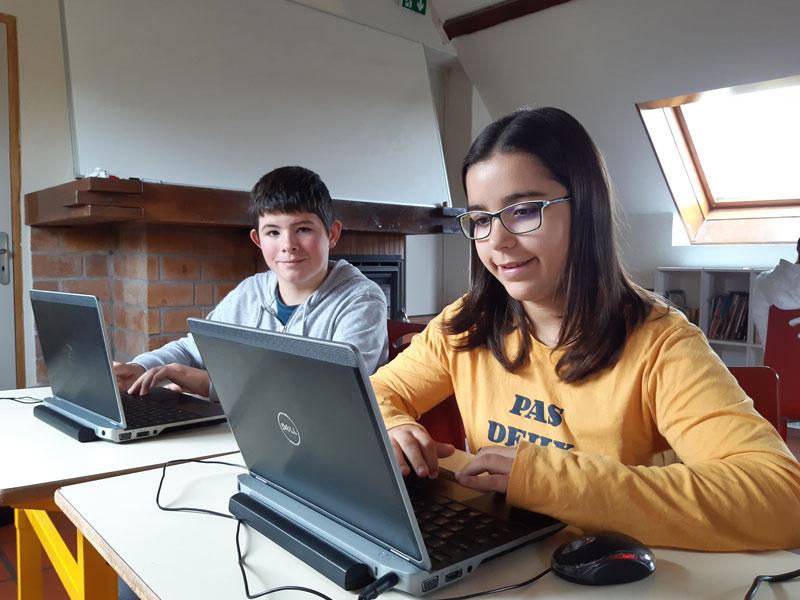 Jeune fille et jeune garçon sur un ordinateur portable en colonie de vacances informatique