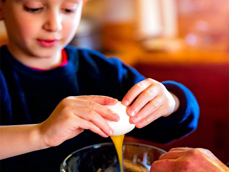 jeune enfant cassant un oeuf en colo cuisine ce printemps