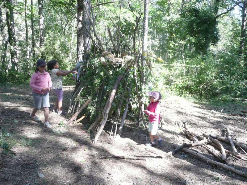 Enfants faisant une cabane dans les bois en colonie de vacance au printemps
