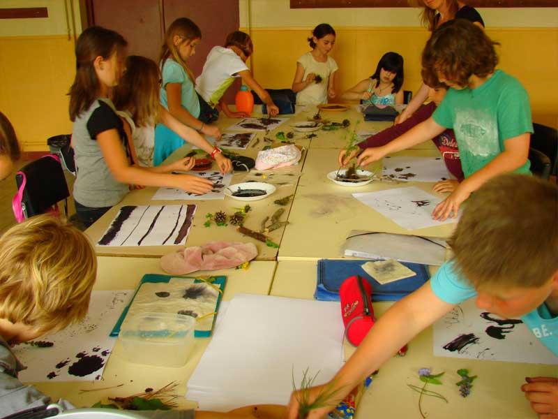 Groupe d'enfants faisant de la peinture en colonie de vacances au printemps