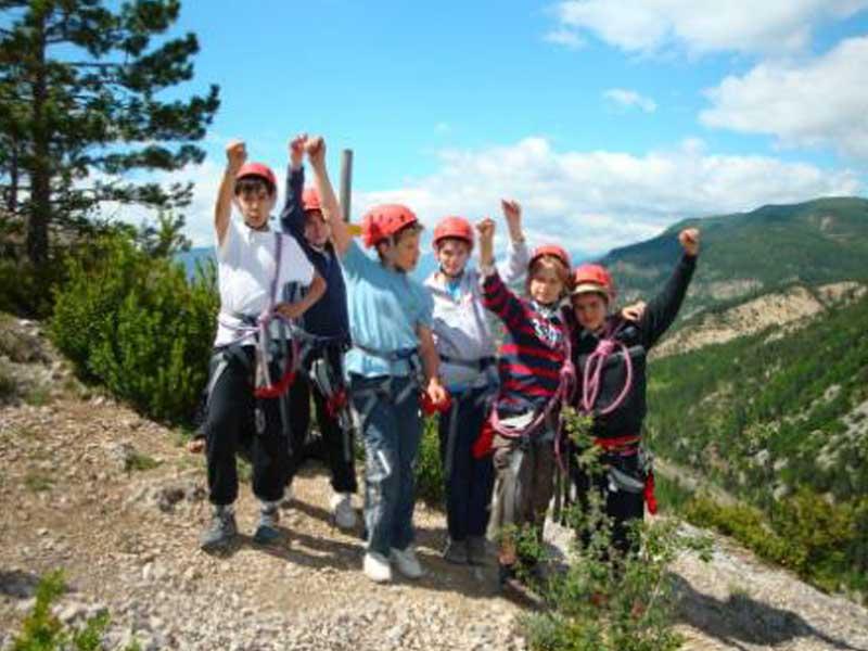 Groupe d'enfants victorieux au sommet d'une montagne après l'activité escalade en colonie de vacances au printemps