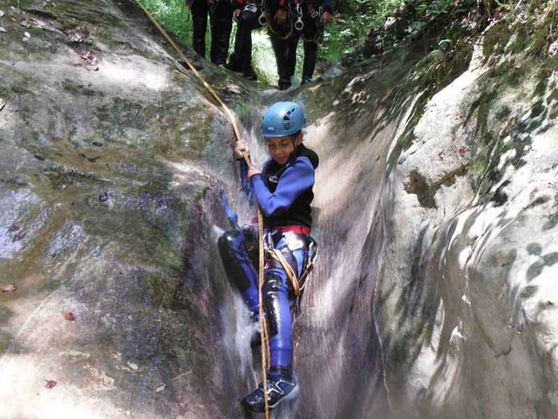 Groupe d'enfants descendant d'un toboggan naturel pendant une activité de canyoning en colonie de vacances