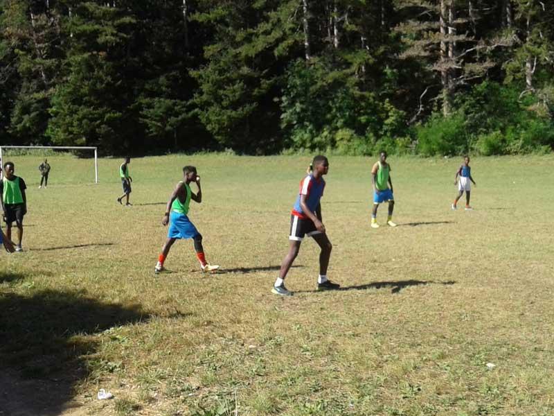 Groupe d'adolescent faisant un entraînement de foot dans un gymnase