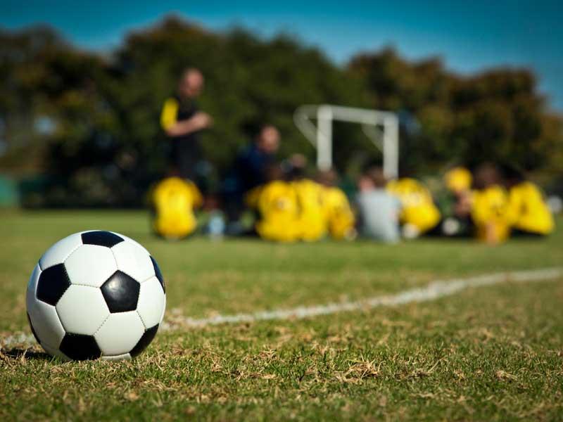 Ballon de football et groupe d'adolescents qui écoute l'entraineur de football