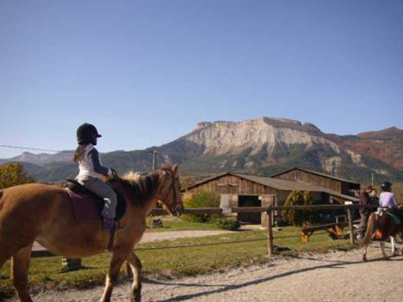 Enfants faisant une balade à cheval en colonie de vacances au printemps