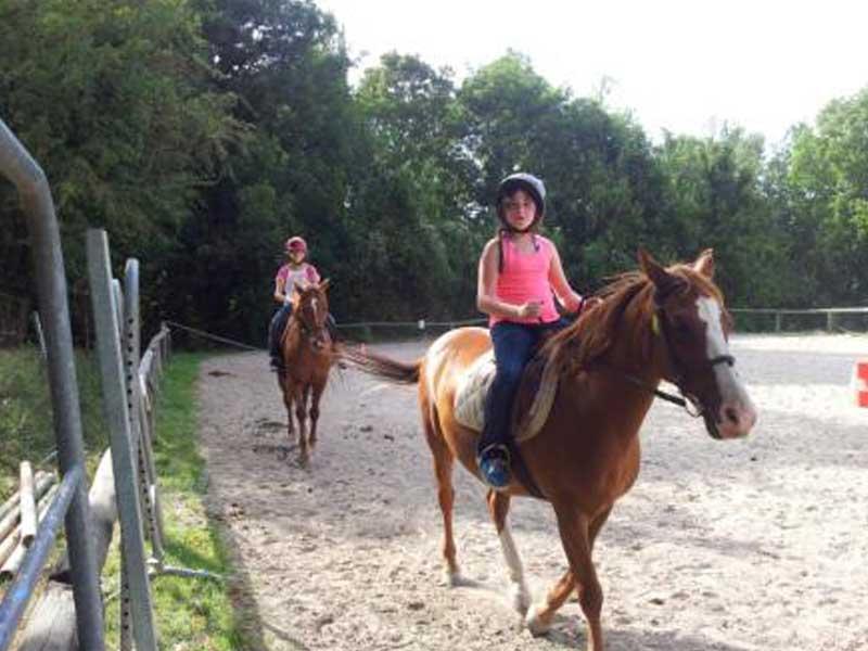 Enfants faisant de l'équitation dans un manège en colonie de vacances