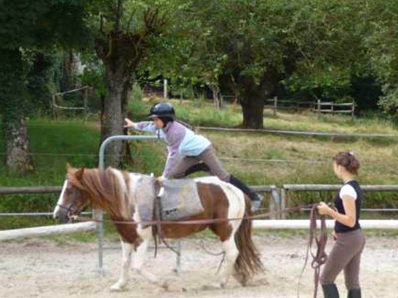 Enfant faisant de la voltige sur un cheval en colonie de vacances