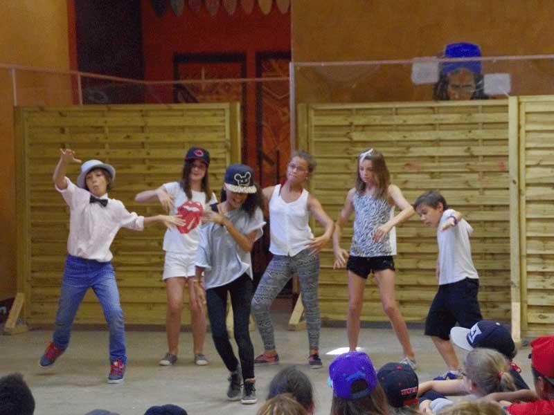 Groupe d'enfants faisant un spectacle de danse devant la colonie de vacances au printemps