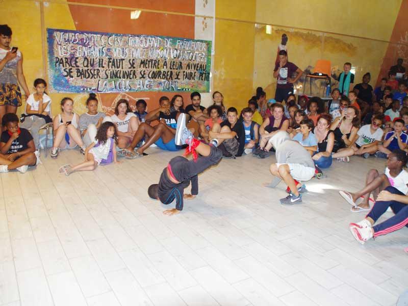 groupe d'enfants faisant des figures de danse devant la colonie de vacances