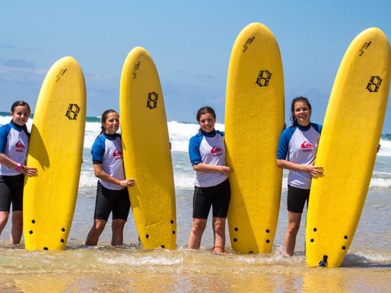 Groupe d'ados avec leur planche de surf en colo ce printemps