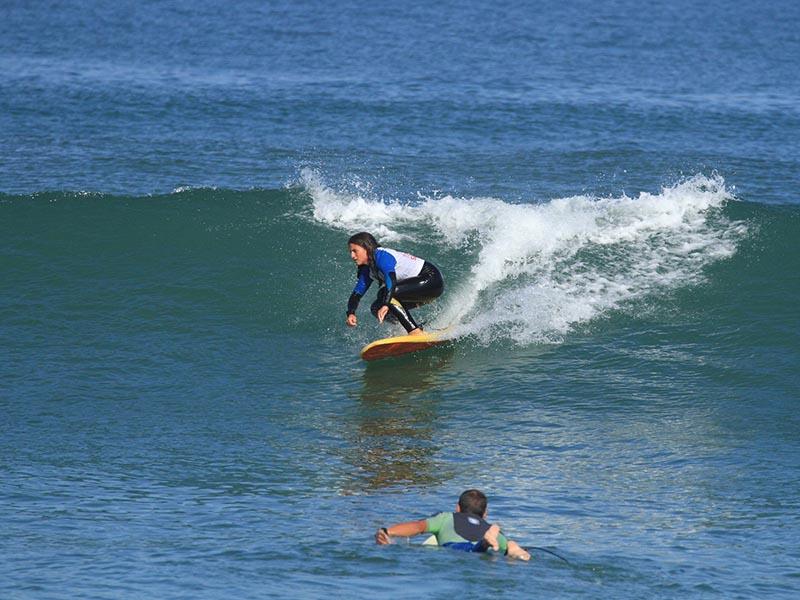 enfants apprenant à faire du surf en colonie de vacances au printemps