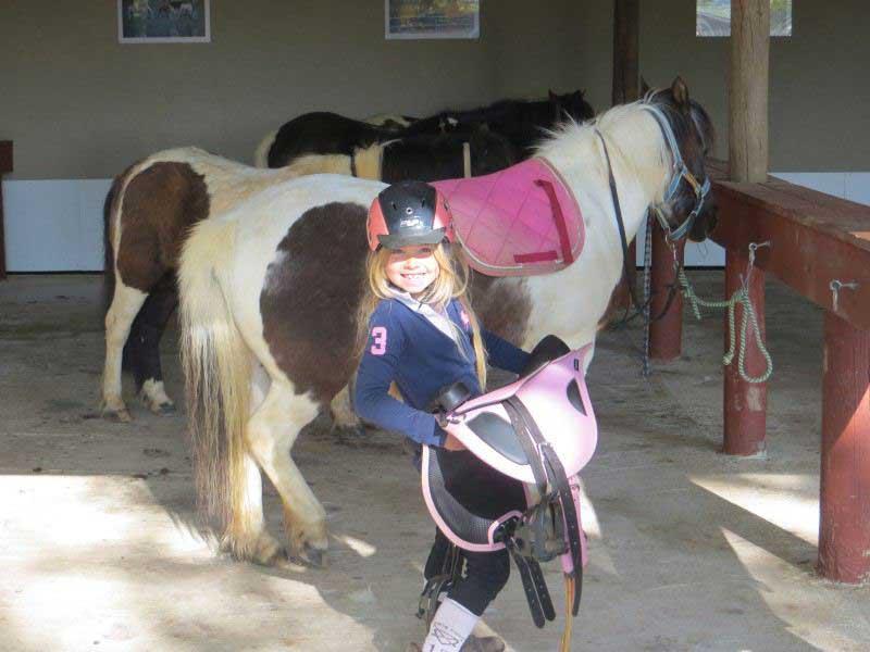 fillette avec son poney en colonie de vacances au printemps
