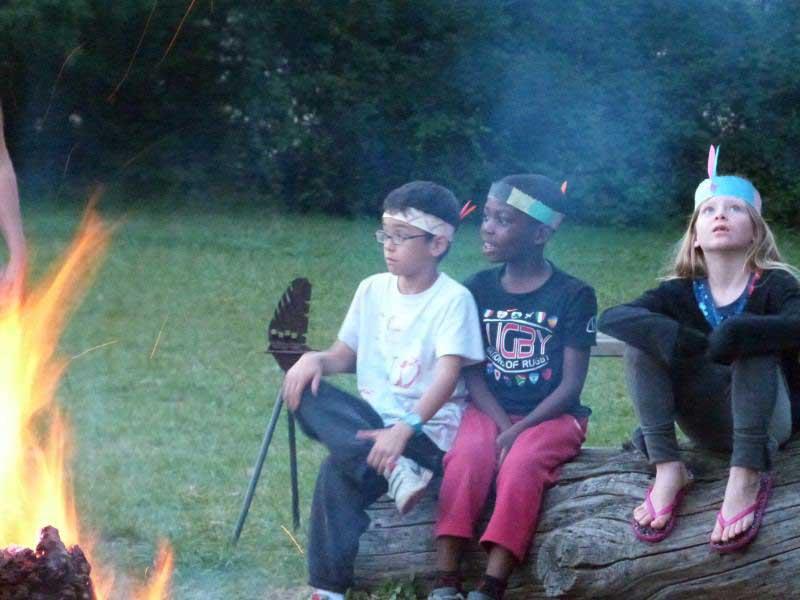 groupe d'enfants autour du feu de camp en colonie de vacances de printemps